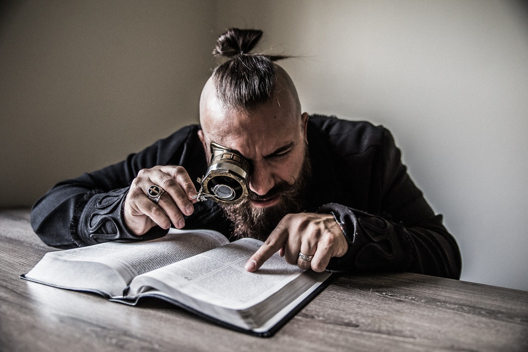man using a magnifying glass to search through a book